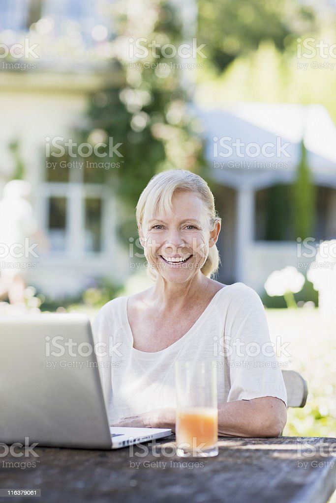 Woman using laptop at patio table royalty-free stock photo