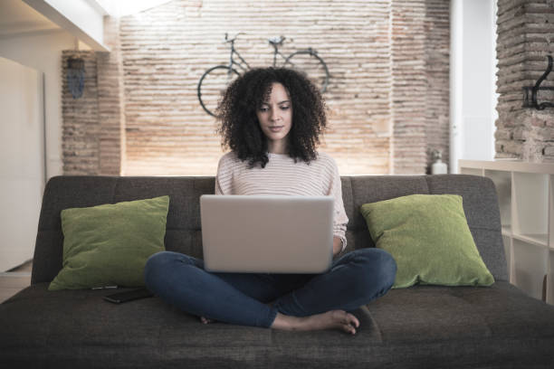 Woman using laptop computer in loft apartment stock photo