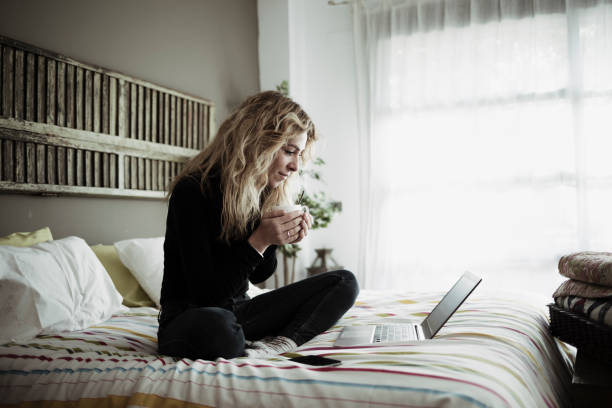 Woman using laptop computer sitting on bed at home stock photo