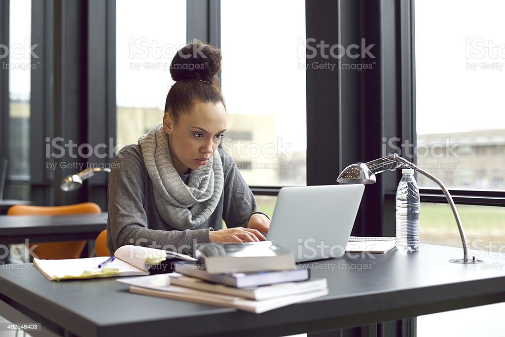 Woman using laptop for taking notes to study stock photo