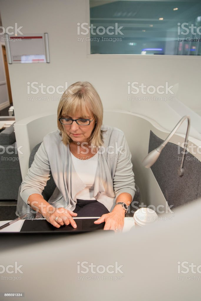 Woman sitting in an office using telecommunications equipment.