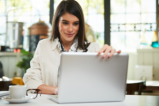 istock Woman using laptop in cafe. 1187342147
