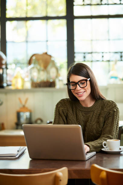 Woman using laptop in cafe. stock photo