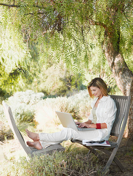 frau mit laptop im garten - garden types stock-fotos und bilder