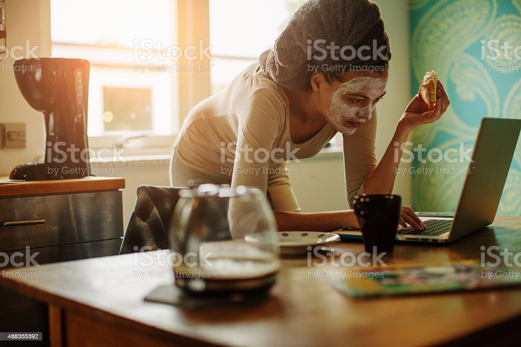Woman using laptop in kitchen stock photo