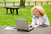 Woman using laptop in park and drink water