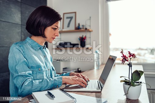 Woman wearing denim shirt using laptop in the office