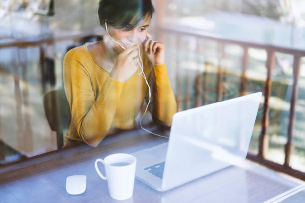 Woman using laptop, making video call stock photo