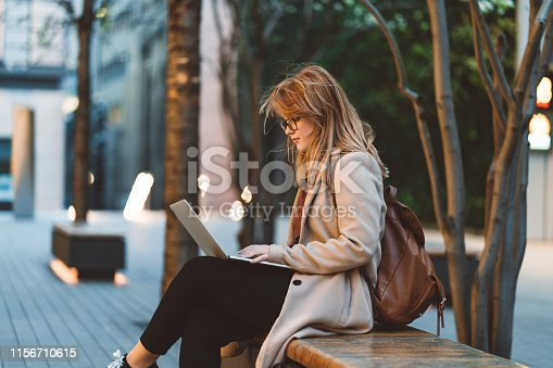 Young businesswoman outside, walking, having a phone conversation, working, having a video call. Student sitting on a bench in a park while using laptop and mobile phone at dusk.