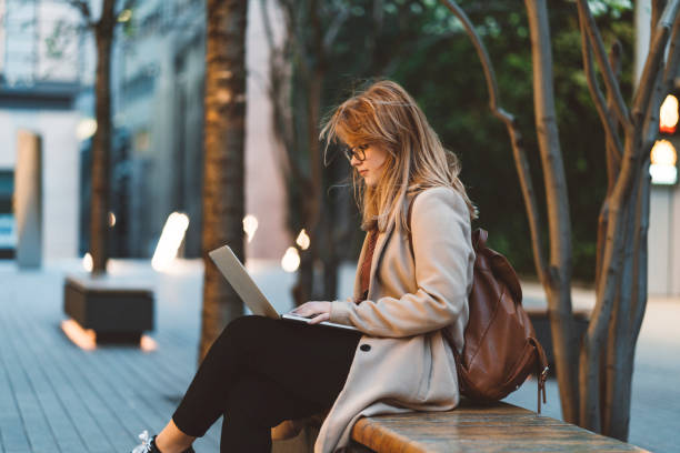 在長凳上使用筆記本電腦的婦女 - small business saturday 個照片及圖片檔