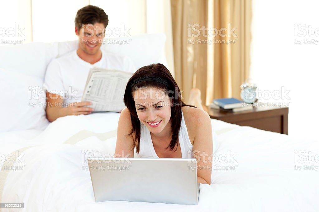 Woman using laptop on her bed royalty-free stock photo