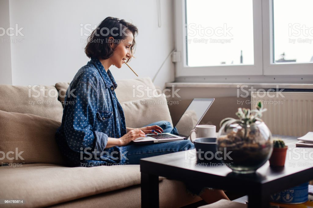 Woman using laptop on sofa and drinking coffee royalty-free stock photo