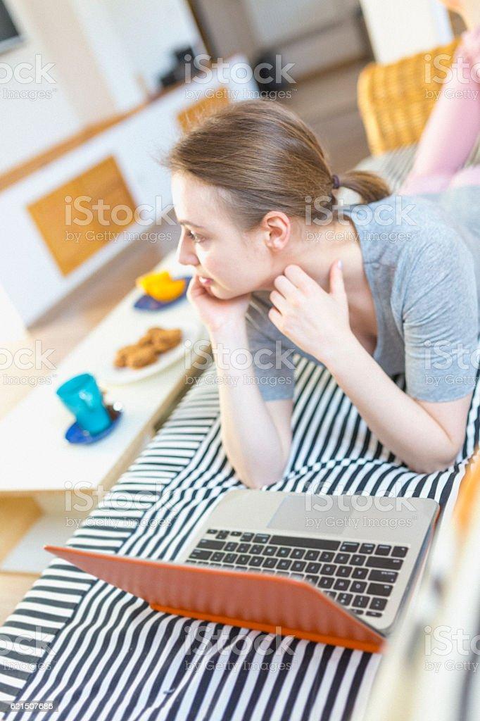 Femme à l'aide d'un ordinateur portable sur un canapé  photo libre de droits