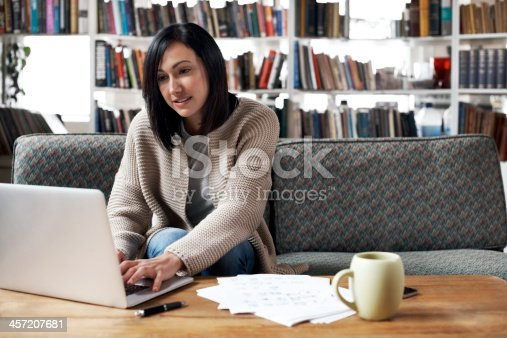 Woman working on her laptop in her cozy loft apartment