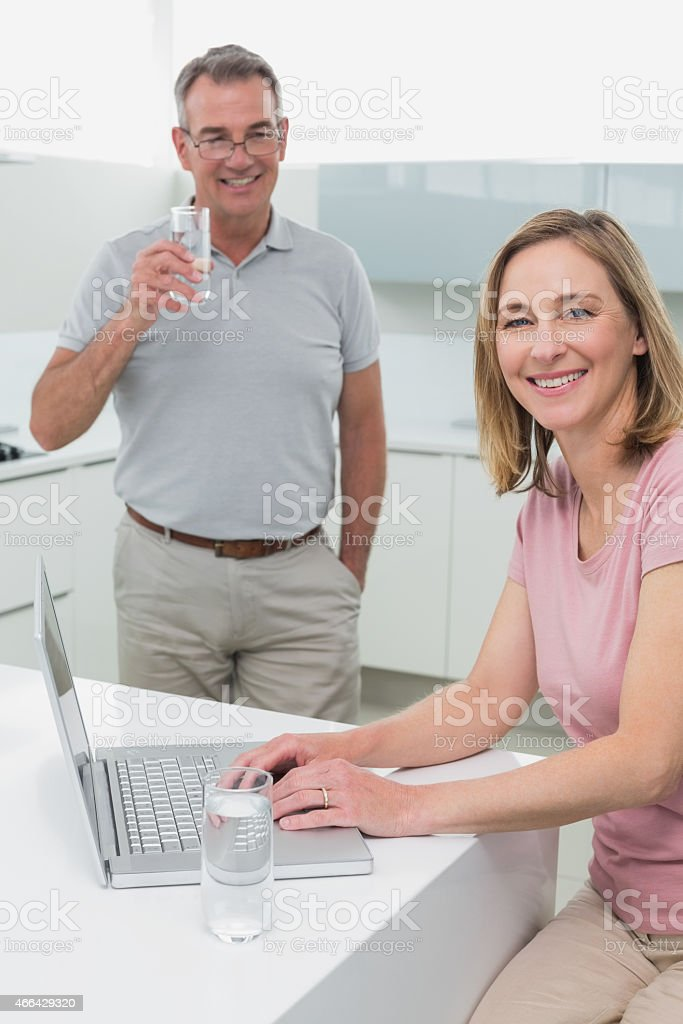 Woman using laptop while man drinking water in kitchen stock photo