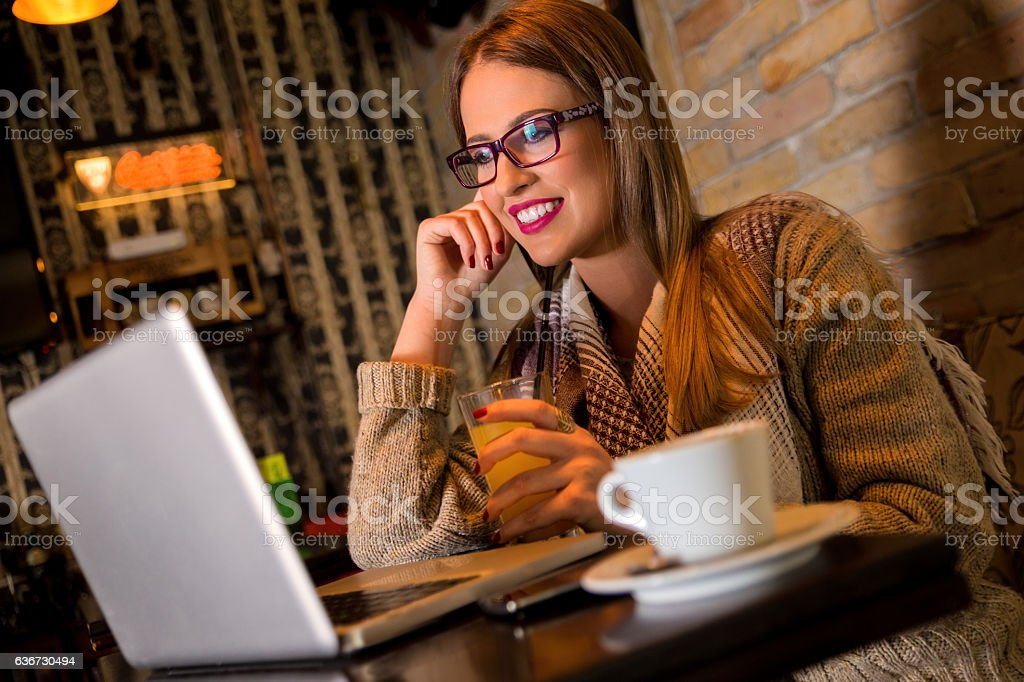 Woman using laptop while sitting at cafe. stock photo