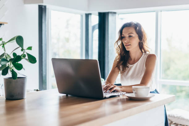 Woman using laptop while sitting at home stock photo