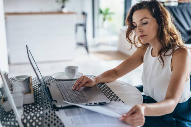mulher usando laptop enquanto senta à mesa. jovem empresária sentada na cozinha e trabalhando no laptop. - mobile - fotografias e filmes do acervo