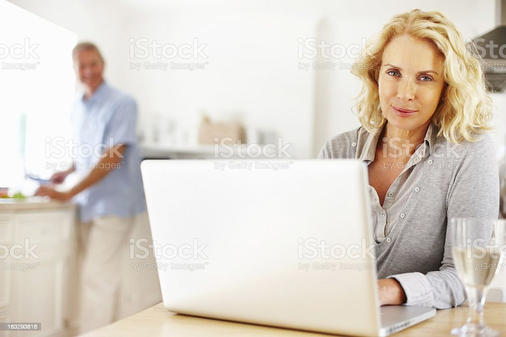 Woman using laptop with a blur man cutting vegetables royalty-free stock photo