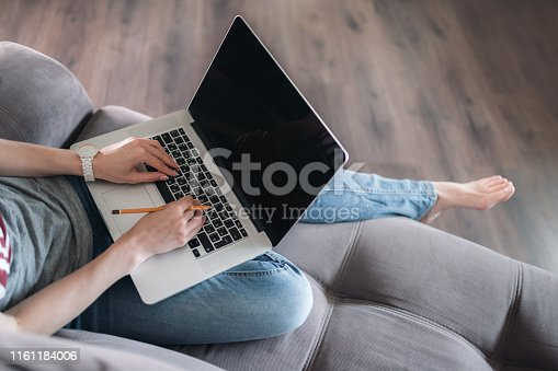 939030682 istock photo Woman using laptop with blank black screen. 1161184006