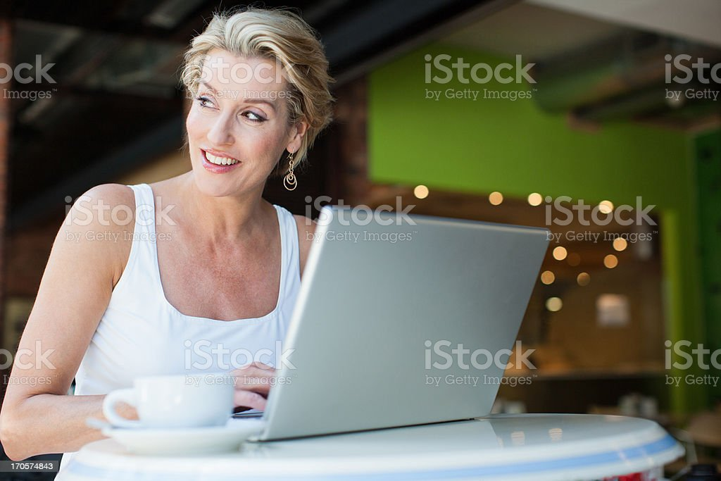 Woman using laptop with coffee in cafe royalty-free stock photo