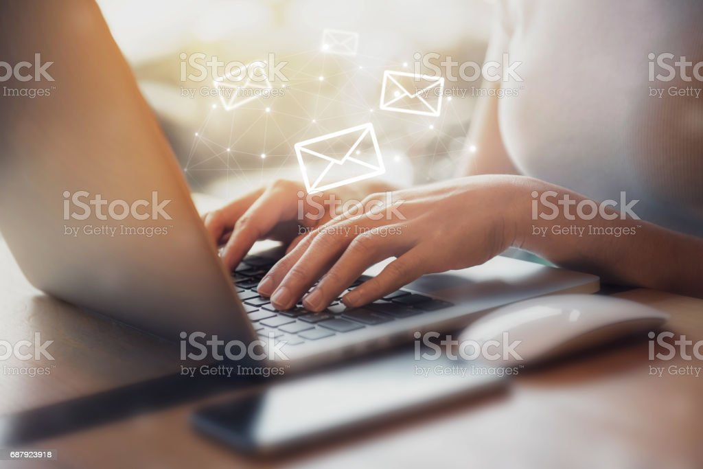 Woman using Laptop with email icon stock photo