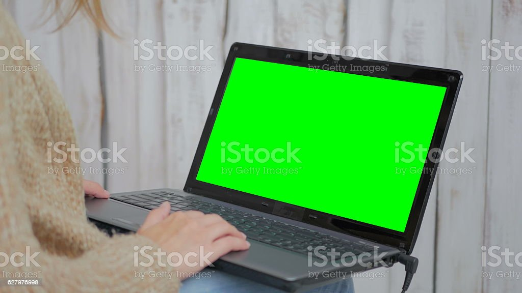 Woman using laptop with green screen stock photo