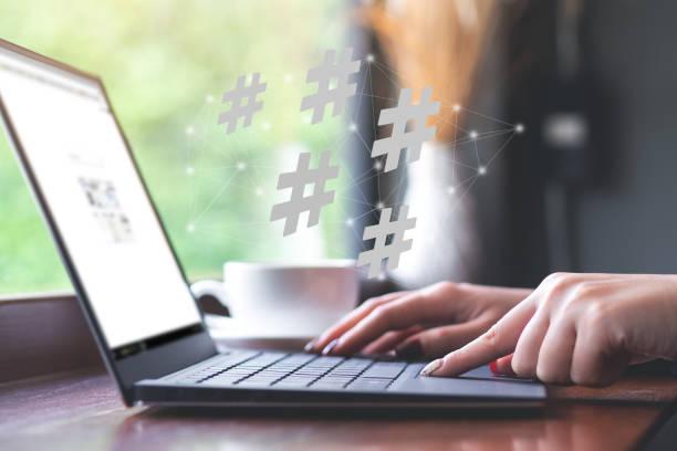 Woman using laptop with hashtag icon. Social media,hashtag concept. stock photo
