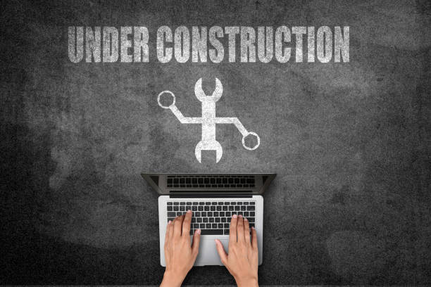 Woman using laptop with website under construction sign - foto stock