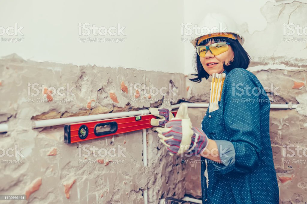 Clever woman repairing r bathroom pipes with positive attitude. Woman...