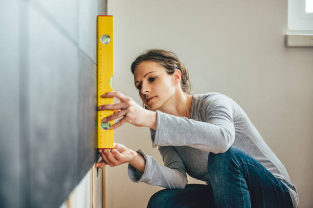 Woman using leveling tool stock photo