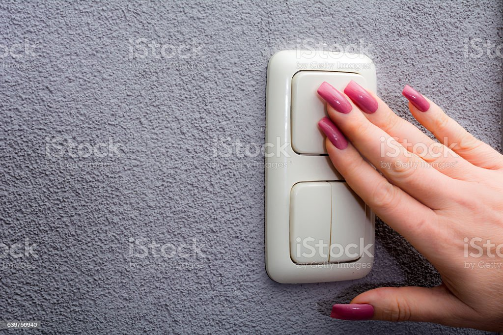 Woman using light switch on grey wall with her hand stock photo