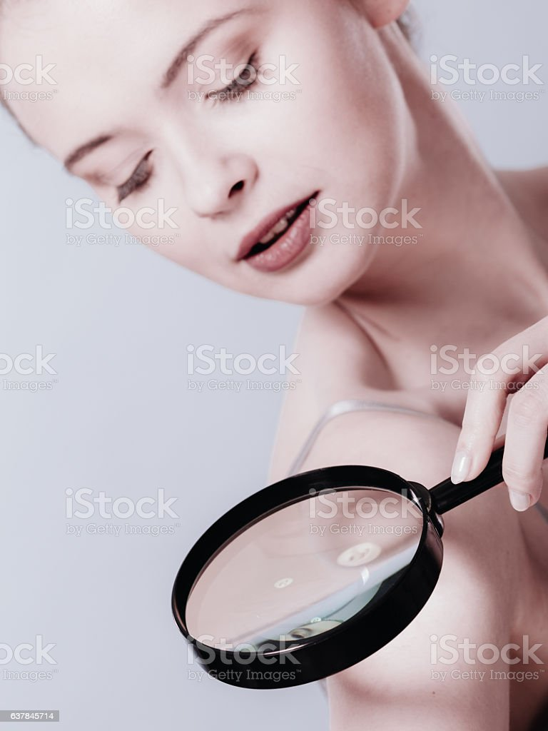 Woman using magnifying glass to examine her moles skin stock photo
