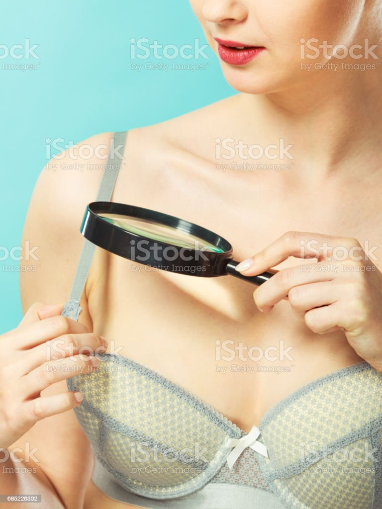 Woman using magnifying glass to examine her moles skin foto de stock royalty-free