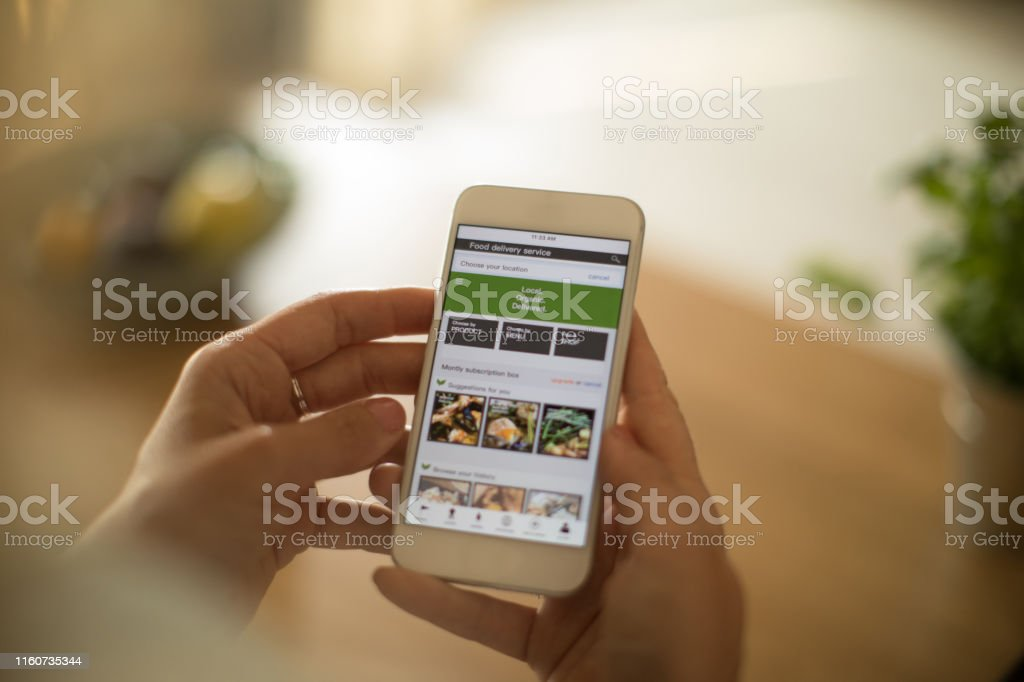 Woman using meal delivery service through mobile app. - Foto stock royalty-free di Adulto