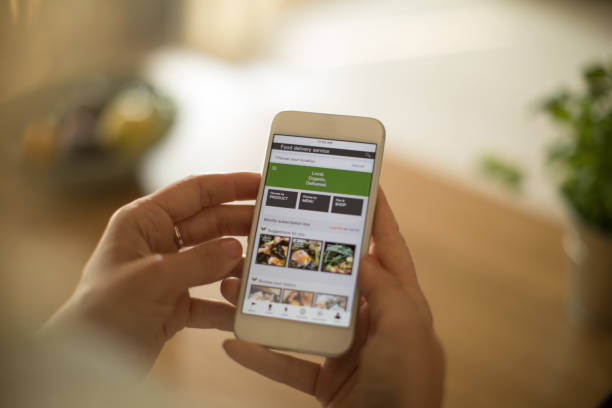 Woman using meal delivery service through mobile app. Woman is using mobile phone to order healthy organic veggies. She want to prepare healthy meal phone stock pictures, royalty-free photos & images