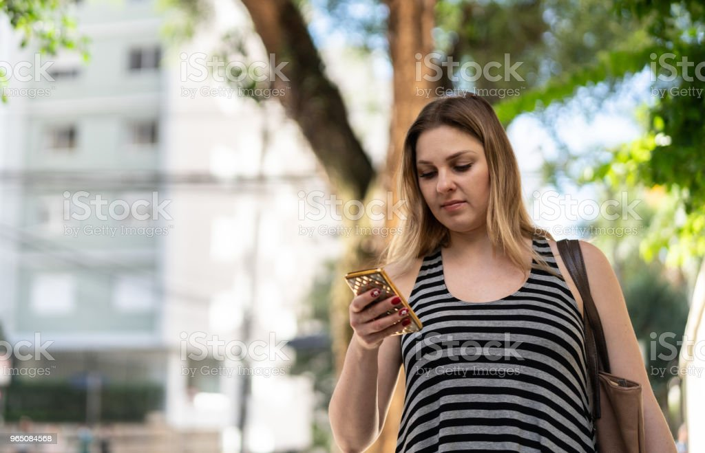 Woman using mobile on street royalty-free stock photo