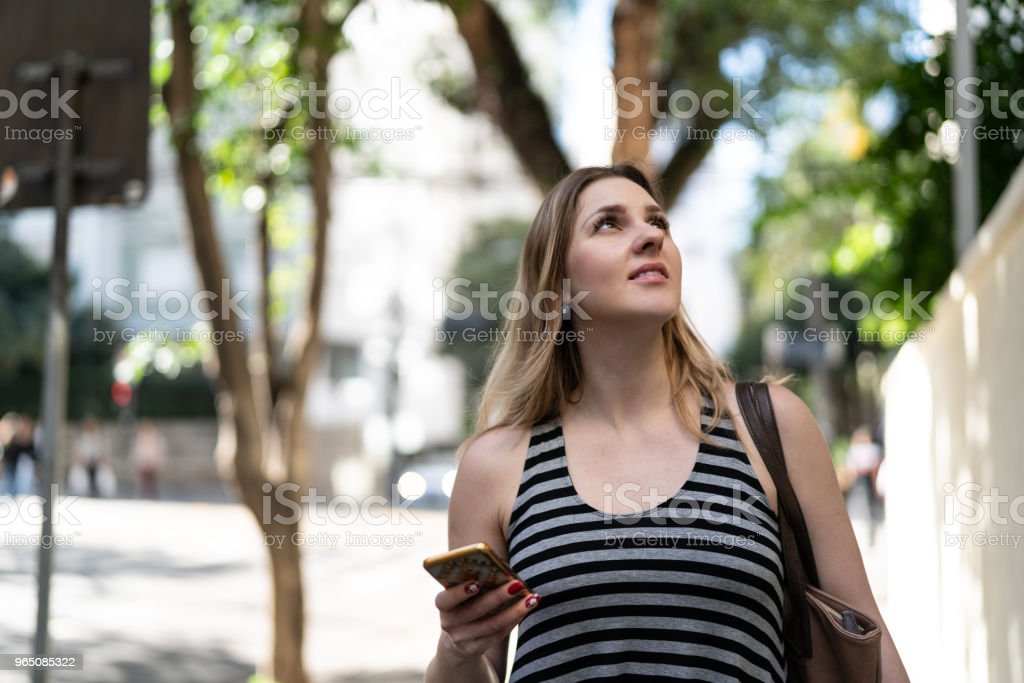 Woman using mobile on street zbiór zdjęć royalty-free
