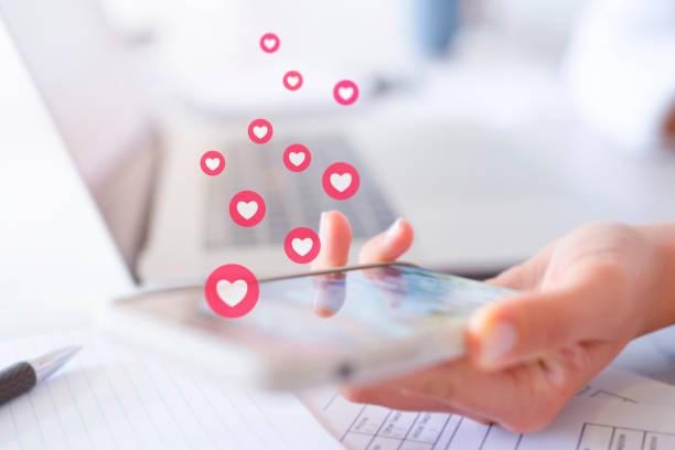 携帯電話を使用して、好きなのを得る女性。 - facebook ストックフォトと画像