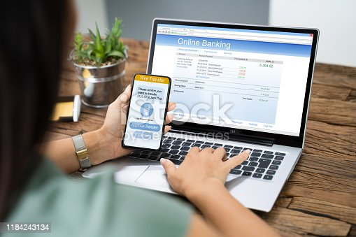 istock Woman Using Mobile Phone App To Authenthificate Bank Transfer 1184243134