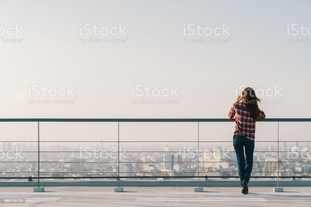 Woman using mobile phone at rooftop during sunset with copy space, communication or lonely people concept stok fotoğrafı