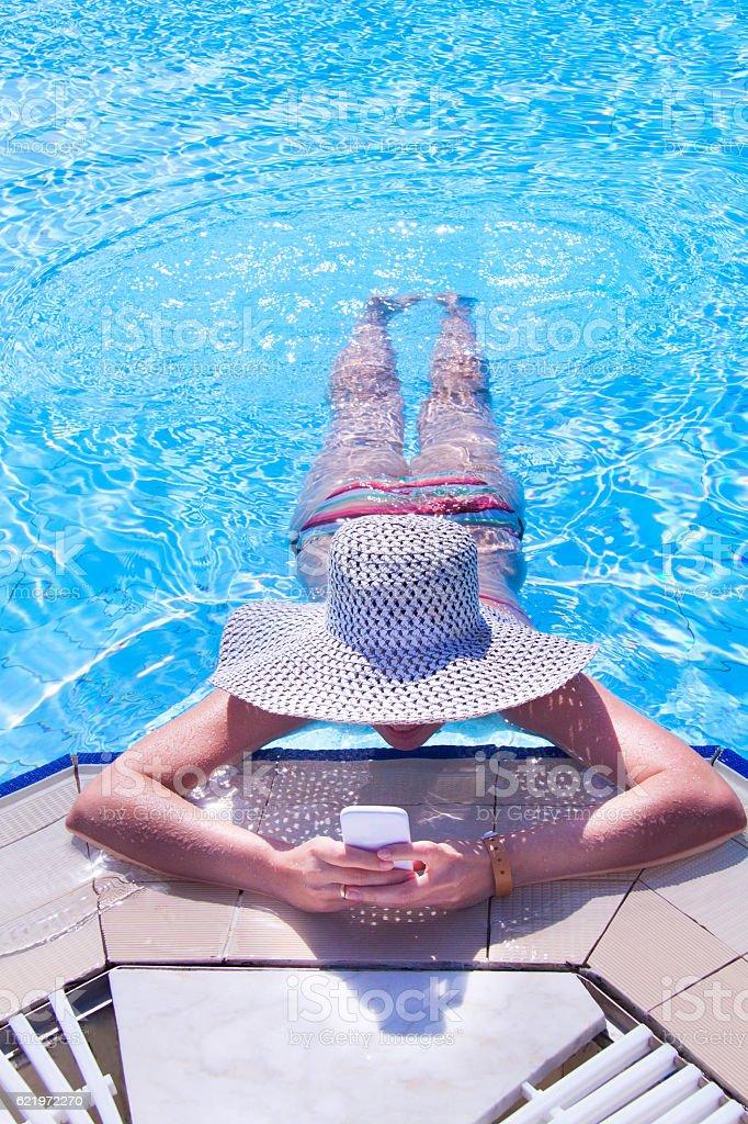 Kobieta przy użyciu telefonu komórkowego na basen  – zdjęcie