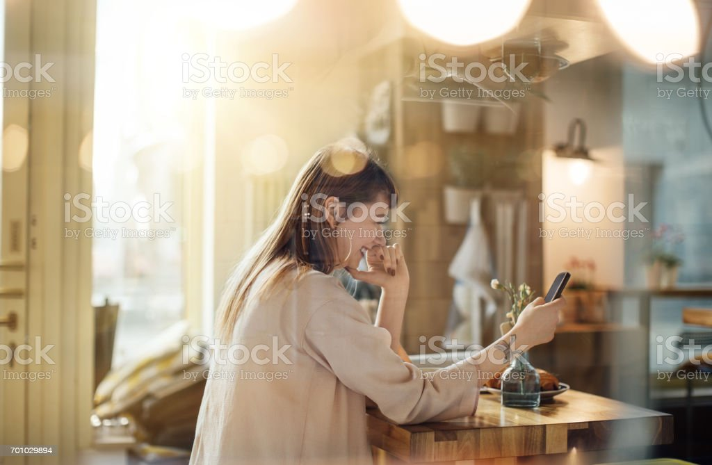 Woman using mobile phone in coffee shop. stock photo