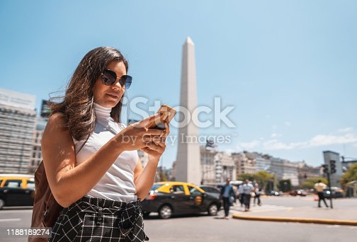Tourist crossing the crosswalk and using phone on the streets of Caba in Buenos Aires, Argentina