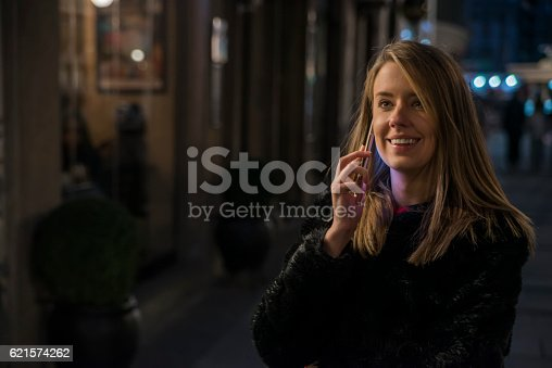 istock Woman using mobile phone in the city, night light background 621574262