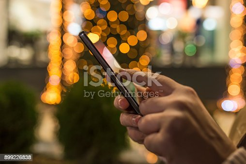 621574390 istock photo Woman using Mobile Phone in the street before christmas 899226838