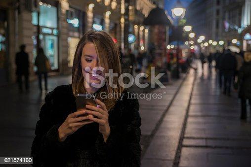 istock Woman using Mobile Phone in the street, night light bokeh 621574160