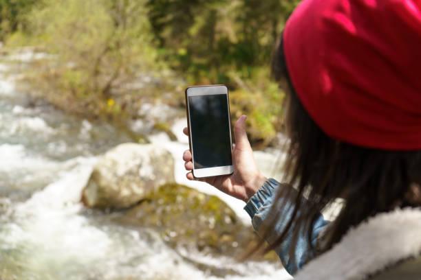 Mujer usando el teléfono móvil en el fondo del río de la montaña - foto de stock
