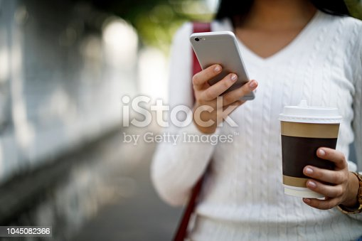 855341616istockphoto Woman using mobile phone on the street 1045082366