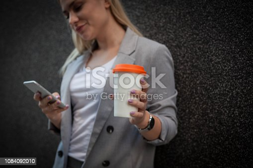 855341616istockphoto Woman using mobile phone on the street . 1084092010
